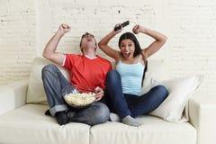 Die jungen Paare, die fernsehen, tragen das Fußballspiel aufgeregte Feiern zur Schau Stockfotos