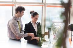 Die jungen Paare, die an leichtem Schlag arbeiten, verschalen im Büro Stockfotografie