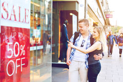 Die jungen Paare, die Shop ` s Fenster in der Stadt mit Verkauf betrachten, fügen hinzu Stockbilder