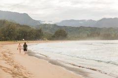 Die jungen Paare, die entlang Hanalei gehen, setzen, Hawaii auf den Strand Lizenzfreies Stockbild