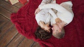 Die jungen Paare fallen auf den Boden in einem gemütlichen Haus auf dem Weihnachtsbaum stock video footage