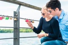 Die jungen Paare, die Vorhängeschloß betrachten, hängen am Geländer lizenzfreie stockfotografie
