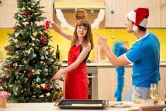 Die jungen Paare, die Weihnachten in der Küche feiern stockbild