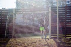 Die Jungen spielen im Hof auf einem besonders ausgerüsteten Fußballplatz auf dem Hintergrund von Wohngebäuden lizenzfreies stockfoto