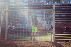 Die Jungen spielen im Hof auf einem besonders ausgerüsteten Fußballplatz auf dem Hintergrund von Wohngebäuden stockbilder