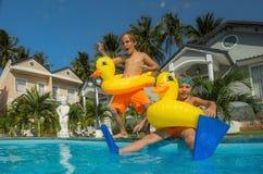 Die Jungen springend in den Swimmingpool Lizenzfreies Stockfoto