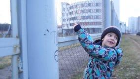 Die Jungenaufstiege über dem hohen Zaun stock video footage
