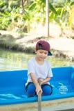 Die Jungenbootfahrt im Park stockfotografie