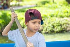 Die Jungenbootfahrt im Park lizenzfreies stockfoto
