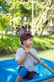 Die Jungenbootfahrt im Park lizenzfreie stockbilder