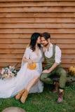 Die Jungvermählten, die in boho Art gekleidet werden, sitzen nahe hölzerner Wand lizenzfreies stockfoto