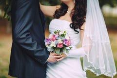 Die Jungvermählten halten in ihren Händen einen Hochzeitsblumenstrauß zwischen einander Nahaufnahme, Fokus auf Blumenstrauß Lizenzfreies Stockbild