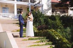 Die Jungvermählten klettern die Schritte zur Hochzeitszeremonie Das Mädchen untersucht durchdacht den Abstand, sie trägt ein Lich Stockfoto