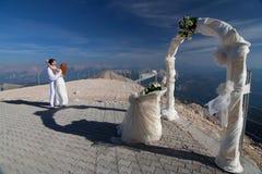 Die Jungvermähltenumarmungen nähern sich dem Hochzeitsbogen Stockfotos