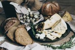 Die Käse, die auf schwarzem Teller und Brot liegen, stellten in der Nähe auf Blauschimmelkäse, Käse mit den Löchern verziert mit  stockfotos