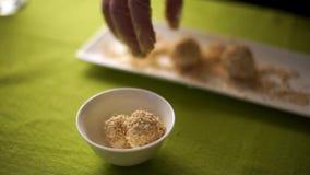 Die Käsebälle, die in den Samen des indischen Sesams abgewischt wurden, verbreiteten auf einer Platte stock video
