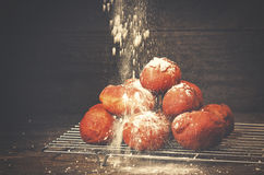 Die köstlichen frisch gebackenen Schaumgummiringe, die mit Puderzucker besprüht werden, gurren Lizenzfreies Stockbild