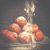 Die köstlichen frisch gebackenen Schaumgummiringe, die mit Puderzucker besprüht werden, gurren Lizenzfreie Stockfotografie