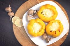 Die köstlichen Gemüsepaprikas, die mit Huhn, Pilze und Käse und Scheiben der Zitrone angefüllt wurden, backten im Ofen Stockbilder