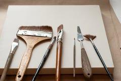 Die Künstler ` s Werkzeuge liegen auf einem leeren Segeltuch Arbeitsaufnahme Lizenzfreie Stockfotografie