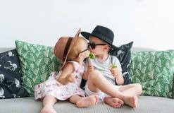 Die küssenden Kinder in den Hüten sitzen auf einem Sofa Lizenzfreies Stockbild