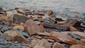 Die Küste mit Steinen, auf denen die Welle findet stock video