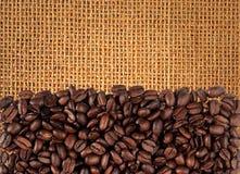 Die Kaffeebohnen, die auf Leinwand zerstreut werden, können benutzt werden Lizenzfreies Stockbild
