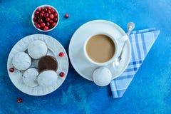 Die Kaffeetasse mit Schokoladenlebkuchen mit weißer Glasur und Moosbeere Stockfotografie