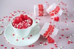 Die Kaffeetasse, die vom Mehrfarbenbonbon voll ist, besprüht Zuckersüßigkeitsherzen und Verpackung Valentinsgruß ` s Tagesgeschen Stockfotos