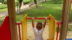 Die Kamera folgt dem Jungen, der unten den Hügel auf dem Spielplatz rollt Glückliches Kind, das auf dem Spielplatz im Park spielt stock video