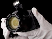 Die Kamera gegen einen dunklen Hintergrund, der Handschuhe hält Lizenzfreies Stockbild