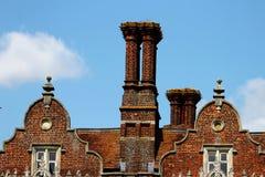 Die Kamine und die Dachspitze eines Tudor-Gebäudes, England Stockbilder