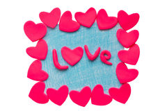 Die Karte des Valentinsgrußes mit Lehmherzen und das Wort lieben auf einem weißen Hintergrund Stockfoto