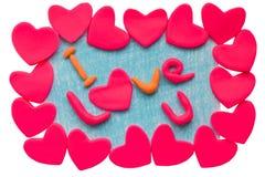 Die Karte des Valentinsgrußes mit Lehmherzen und der Text I lieben U auf einem weißen Hintergrund Lizenzfreie Abbildung