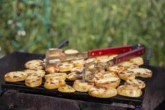 Die Kartoffeln, die mit Bechern geschnitten werden, werden auf einem Gitter gebraten stockfotografie