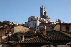 Die Kathedrale, die aus mit Ziegeln gedeckten Dächern heraus, Florenz, Italien schaut Stockfotografie