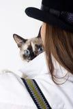 Die Katze schaut heraus von hinten das Mädchen im Hut Stockfotografie