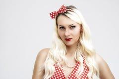 Die kaukasische weibliche blonde Frau, die in der Pinup-Art aufwirft, kleidet wieder Stockfotografie