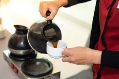 Die Kellnerin gießt den Kaffee lizenzfreie stockfotografie