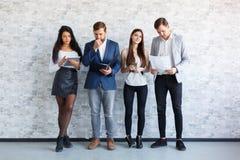 Die Kerle und ein Mädchen sind, halten stehend und Dokument, Ordner, eine Tablette und Telefone zuhause stockbild