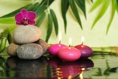 Die Kiesel, die im Zenlebensstil auf dem links mit einer Orchidee an der Spitze vereinbart wurden und drei beleuchteten rosa Kerz Stockfoto
