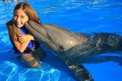 Die Kinder des kleinen Mädchens, die ein lächelndes glückliches Kind des Gesichtes des herrlichen Delphinflippers küssen, schwimm Lizenzfreie Stockbilder