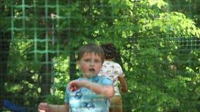 Die Kinder, die auf die Trampoline im Park springen, haben Spaß stock footage
