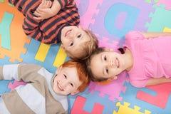 Die Kinder, die auf Rückseiten auf Spaß liegen, scherzt Alphabetmatte lizenzfreie stockfotos