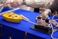 Die Kinder, die lernen, auf Spielzeug festzumachen, versenden Modell an der Segelschule Lizenzfreie Stockbilder