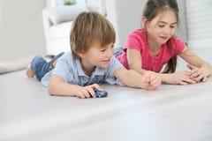Die Kinder, die mit Auto spielen, spielt das Lügen auf dem Boden Stockbilder