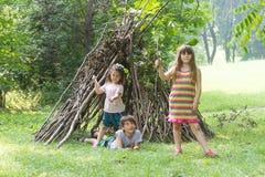 Die Kinder, die nahe bei hölzernem Stock spielen, bringen das Aussehen wie indische Hütte unter, Stockbild