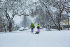 Die Kinder, die einen Schlitten hinunter einen ruhigen Schnee ziehen, bedeckten Straße Lizenzfreie Stockfotos