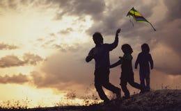 Die Kinder, die mit Drachen auf Sommersonnenuntergangwiese spielen, silhouettierten stockfotos
