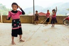 Die Kinder, die rosa T-Shirt tragen, spielen Seilspringen auf konkretem Boden im Sommer an Sa-PA, Vietnam Stockbilder